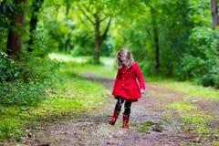 Bambina che cammina nella pioggia Fotografia Stock
