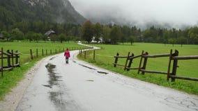 Bambina che cammina in pioggia sulla strada campestre archivi video