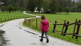 Bambina che cammina in pioggia sulla strada campestre stock footage