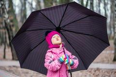 Bambina che cammina sotto l'ombrello in un parco della città immagine stock