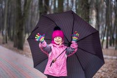 Bambina che cammina sotto l'ombrello in un parco della città fotografia stock libera da diritti