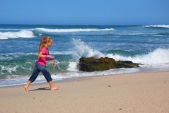 Bambina che cammina sulla spiaggia Fotografie Stock