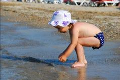 Bambina che cerca le coperture sulla spiaggia Immagini Stock Libere da Diritti