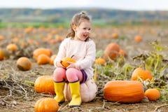 Bambina che coltiva sulla toppa della zucca Fotografia Stock