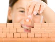 Bambina che costruisce una parete Fotografia Stock