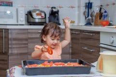 Bambina che cucina alimento nella cucina Fotografie Stock Libere da Diritti