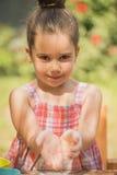 Bambina che dà farina alla macchina fotografica Fotografia Stock