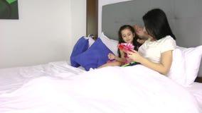 Bambina che dà un regalo a sua madre nella camera da letto stock footage