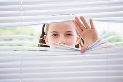 Bambina che dà una occhiata attraverso i ciechi immagine stock