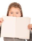 Bambina che dà una occhiata da dietro un libro aperto Fotografie Stock Libere da Diritti