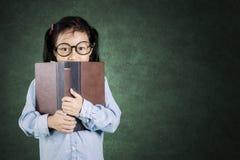 Bambina che dà una occhiata dietro il libro Immagine Stock