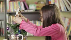 Bambina che decora l'albero di Natale archivi video
