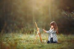 Bambina che dipinge all'aperto fotografia stock