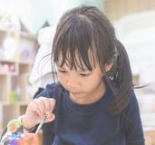 Bambina che dipinge una bambola nell'aula di arte Fotografia Stock