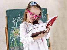 Bambina che disegna un'immagine con gesso sulla lavagna Immagini Stock Libere da Diritti
