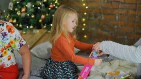 Bambina che disimballa presente vicino all'albero di Natale archivi video