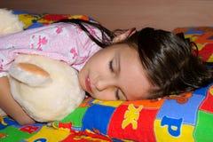 Bambina che dorme con l'orso dell'orsacchiotto immagini stock libere da diritti
