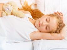 Bambina che dorme nel letto bianco Immagine Stock
