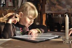 Bambina che esamina il menu Immagine Stock