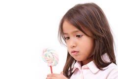 Bambina che esamina la caramella dolce della caramella gommosa e molle Immagini Stock