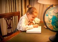 Bambina che fa compito di geografia Immagini Stock