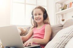 Bambina che fa compito sul computer portatile a casa Immagine Stock Libera da Diritti