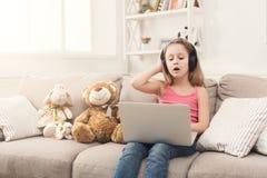 Bambina che fa compito sul computer portatile a casa Fotografia Stock Libera da Diritti