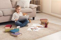 Bambina che fa compito sul computer portatile, sedentesi sul pavimento Fotografia Stock