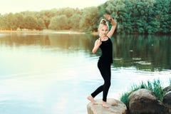 Bambina che fa forma fisica, pilates sulla sponda del fiume immagini stock