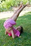 Bambina che fa ginnastica sul prato Fotografia Royalty Free