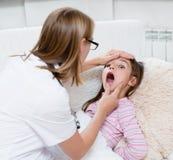 Bambina che fa la sua esaminare gola dal professionista del settore medico-sanitario fotografia stock libera da diritti