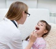 Bambina che fa la sua esaminare gola dal professionista del settore medico-sanitario immagini stock libere da diritti