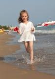 Bambina che funziona giù la spiaggia. Fotografie Stock