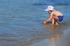 Bambina che gioca in acqua sulla spiaggia Immagine Stock