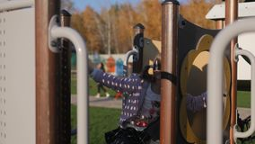 Bambina che gioca al campo da giuoco in parco, autunno