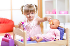 Bambina che gioca al dottore con il suo neonato fotografia stock