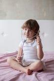 Bambina che gioca al dottore sul letto, la bambina con una st fotografia stock