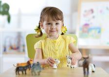 Bambina che gioca con i giocattoli animali Fotografia Stock