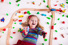 Bambina che gioca con i treni di legno Fotografia Stock