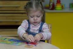 Bambina che gioca con il conteggio dei bastoni sull'aritmetica immagine stock libera da diritti