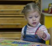 Bambina che gioca con il conteggio dei bastoni sull'aritmetica fotografia stock libera da diritti