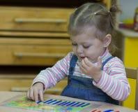 Bambina che gioca con il conteggio dei bastoni sull'aritmetica fotografie stock libere da diritti