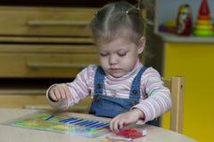Bambina che gioca con il conteggio dei bastoni sull'aritmetica fotografia stock