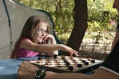 Bambina che gioca con il suo campo all'aperto del bordo di progetti del padre Immagine Stock