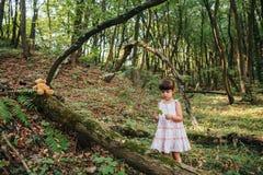Bambina che gioca con il suo orso nella foresta Fotografia Stock