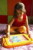 Bambina che gioca con il tavolo da disegno magnetico, Pune, maharashtra, India fotografia stock libera da diritti