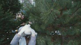 Bambina che gioca con l'orso ed i tiri della peluche su al fondo dell'abete stock footage