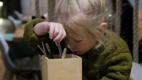 Bambina che gioca con la forchetta ed il cucchiaio in caffè stock footage