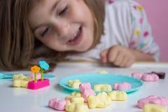 Bambina che gioca con le caramelle fotografia stock