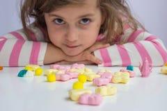 Bambina che gioca con le caramelle immagine stock